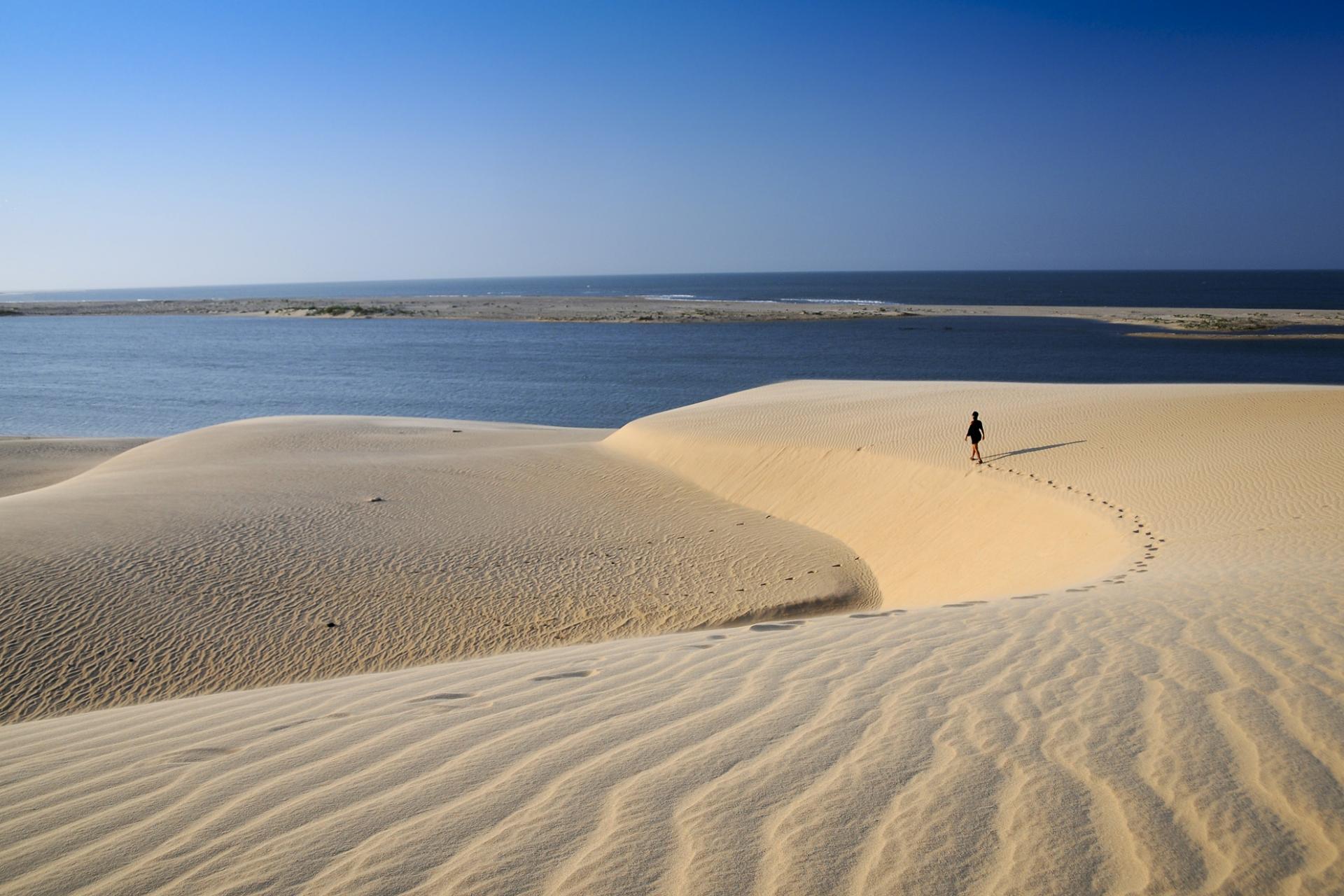 Einsamer Wanderer in den Sanddünen von Jericoacoara hinterlässt Fußspuren auf dem Weg zum Meer