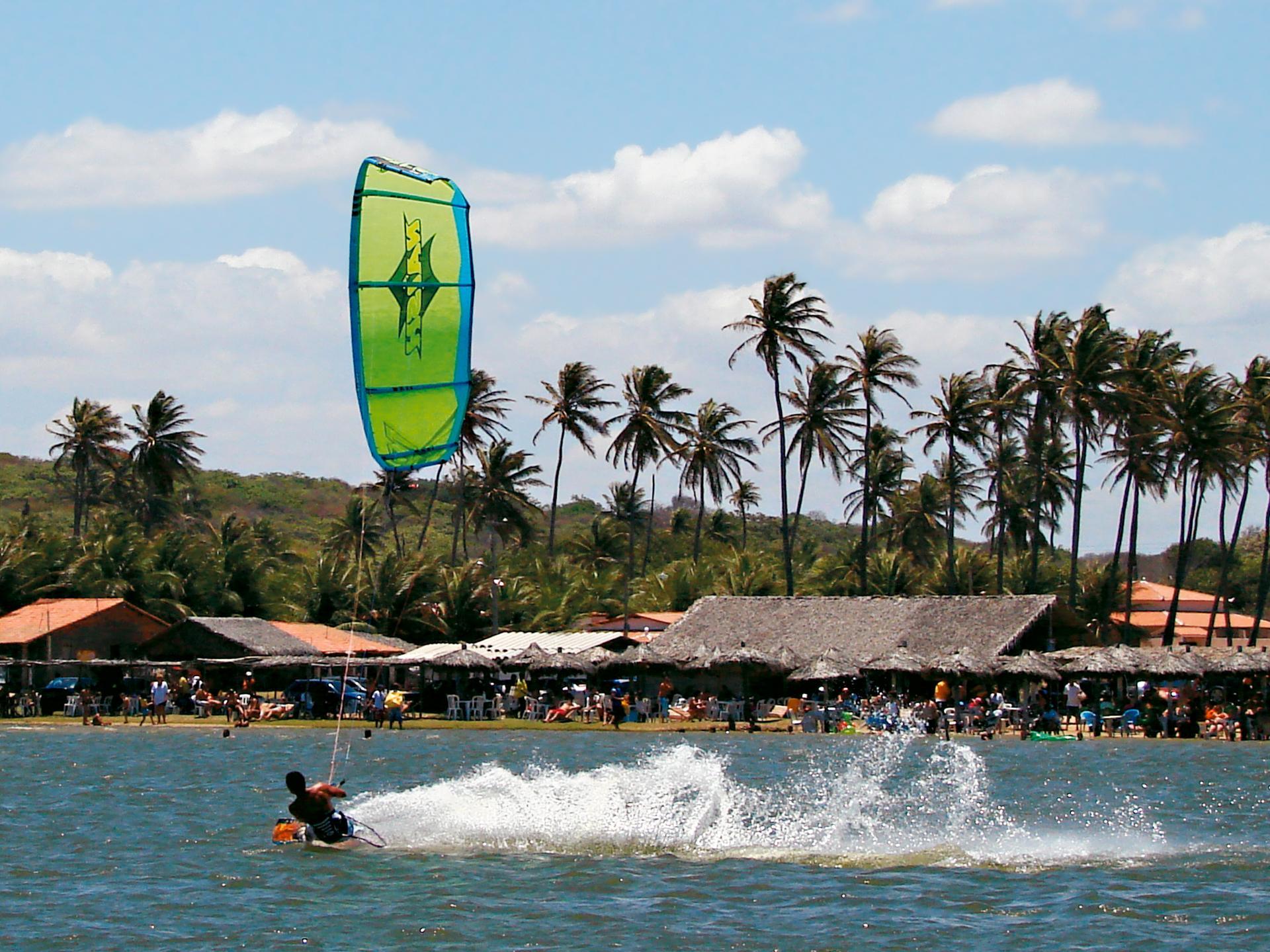 Sportlicher Windsurfer am palmengesäumten Strand von Cumbuco in Aktion