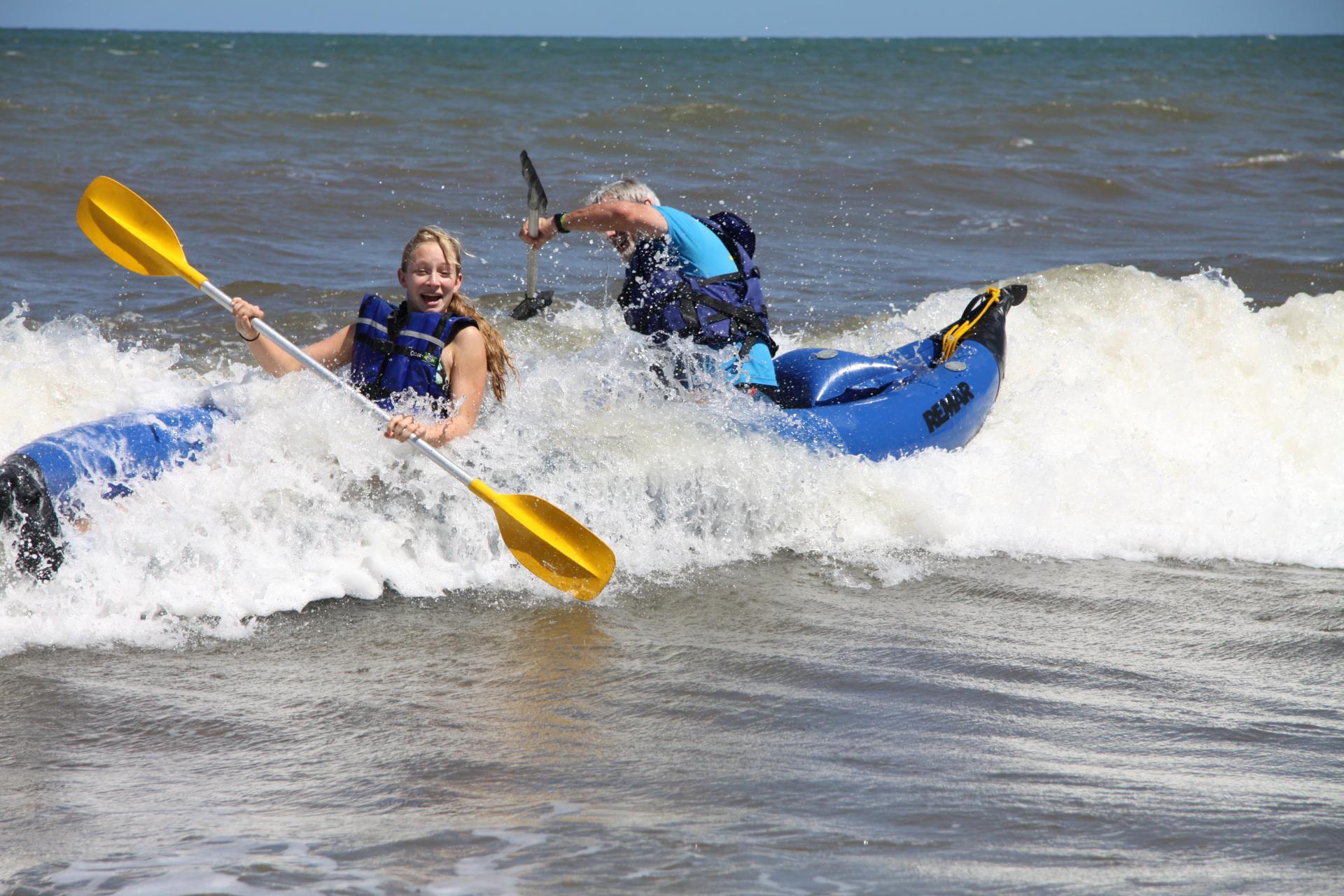 Zwei Kanuten im Abenteuer reiten auf dem Ausläufer einer Welle in Pratigi, Bahia