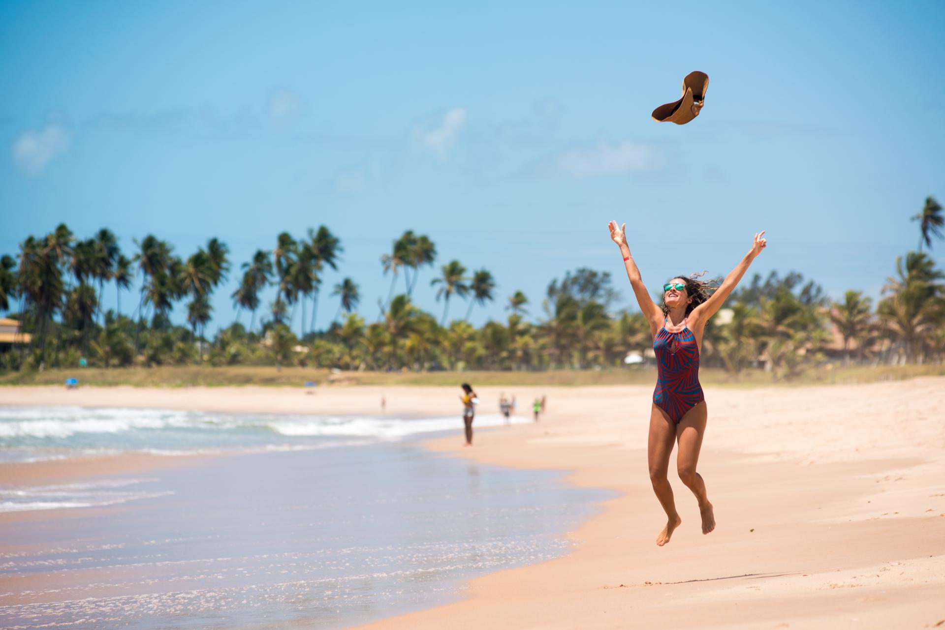 Lifestyle pur in Bahia: Urlauberin beim freudigen Luftsprung am Strand von Guarajuba