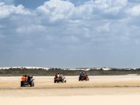 Drei Buggys fahren hintereinander über den Sandstrand