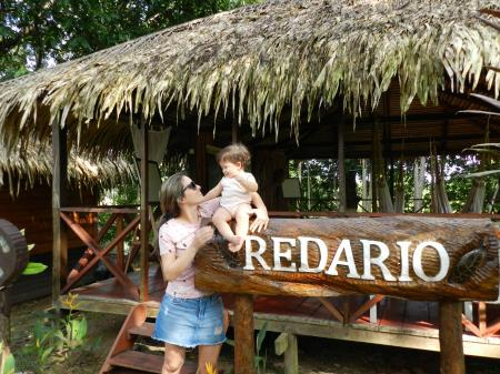 Frau und Kleinkind vor Bungalow mit Hängematten der Turtle Lodge
