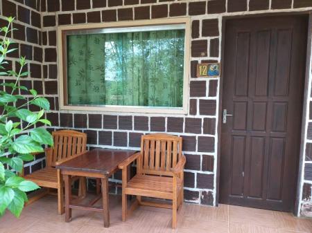 Zwei Holzstühle und Tisch vor Bungalow der Turtle Lodge