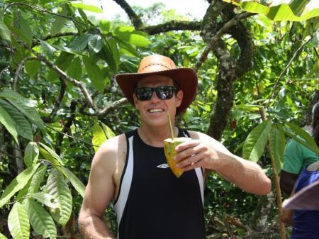 Tourist in Bahia trinkt Kakaohonig aus einer Kakaofrucht