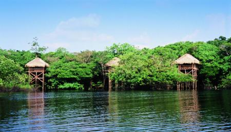 Hütten der Juma Amazon Lodge mit Blick auf den See