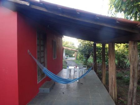 Ein rotes Bungalow mit Hängematte in der Pousada Fazenda Rio Negro