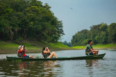 Uakari Lodge drei Menschen auf Kanufahrt auf dem Fluss