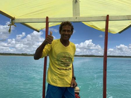Guide auf überdachtem Boot auf dem Wasser vor dem Strand von Praia da Lage