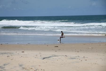 Junger Mann spielt Fußball am Strand von Itacare