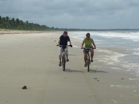 Zwei Radler fahren am Strand
