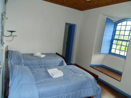 Ein Zimmer mit zwei Betten in der Kloster-Pousada Serra do Caraca auf der Goldroute in Brasilien