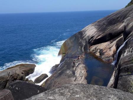Besucher erleben den natürlicher Pool unter dem Wasserfall Saco Bravo an der Costa Verde